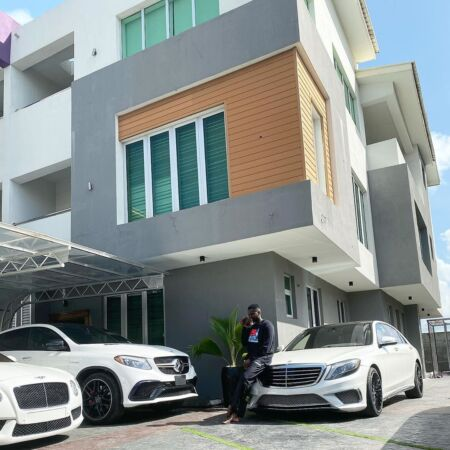 Kizz Daniel poses with his cars next to his house